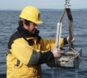 photo of scientist with sediment sampling equipment